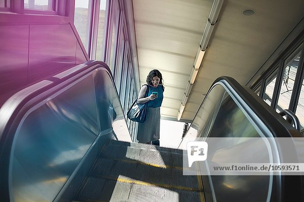 Mittlere erwachsene Frau mit Rolltreppe  Smartphone haltend  erhöhte Ansicht