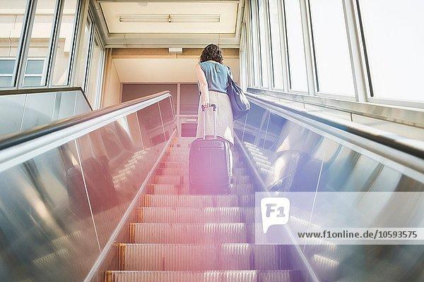 Mittlere erwachsene Frau mit Rolltreppe  Rollkoffer haltend  Rückansicht  Tiefblick
