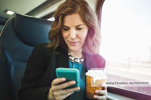 Mittlere erwachsene Frau im Zug  mit Smartphone  Kaffeetasse haltend