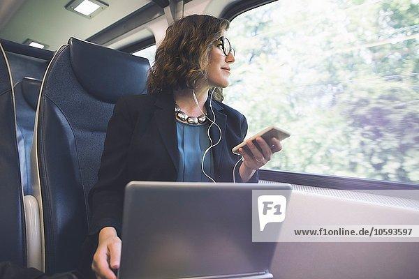 Mittlere erwachsene Frau im Zug  Smartphone  Laptop vor sich haltend