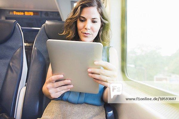 Mittlere erwachsene Frau im Zug mit digitalem Tablett