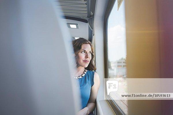 Mittlere erwachsene Frau im Zug  aus dem Fenster schauend