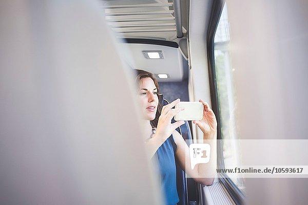 Mittlere erwachsene Frau im Zug  die mit dem Smartphone durchs Fenster fotografiert.