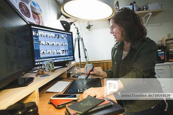 Mittlere erwachsene Frau am Schreibtisch sitzend  mit Grafiktablett  auf den Computerbildschirm schauend