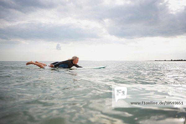 Seniorin auf dem Surfbrett im Meer  Paddleboarding