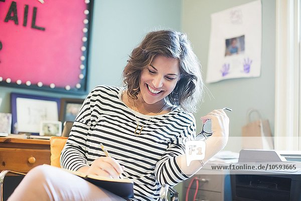 Mittlere erwachsene Frau sitzend  im Buch schreibend