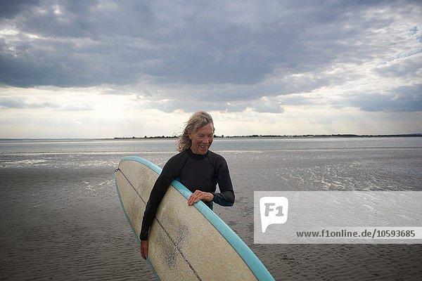Seniorenfrau  die vom Meer aus geht und Surfbrett trägt
