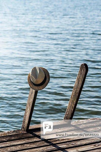 Panamahut hängend an der Treppe des Holzpiers neben dem See Panamahut hängend an der Treppe des Holzpiers neben dem See