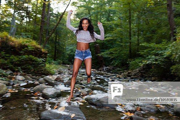 Porträt einer fröhlichen jungen Frau  die über Waldfelsen springt.