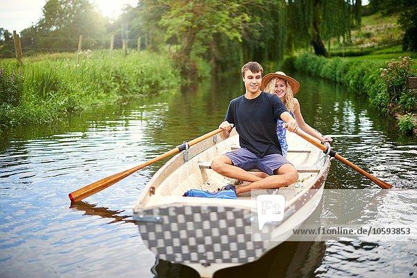 Portrait eines jungen Paares beim Rudern auf dem Landfluss