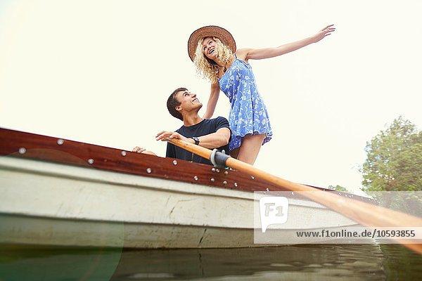 Tiefblick auf die junge Frau im Ruderboot auf dem Fluss