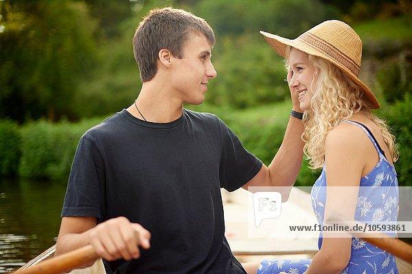 Romantisches junges Paar Ruderboot auf dem Landfluss