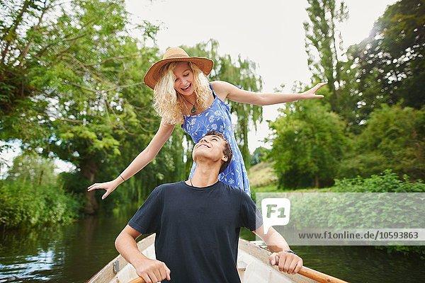 Junge Frau mit Freund im Ruderboot auf dem Fluss stehend