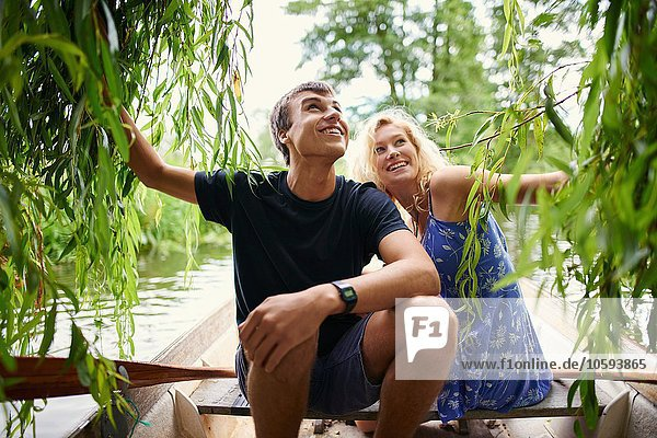 Junges Paar berührt Weidenlaub vom Ruderboot auf dem Landfluss