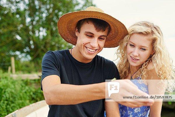 Junges Paar schaut auf Insekt im Fluss-Ruderboot
