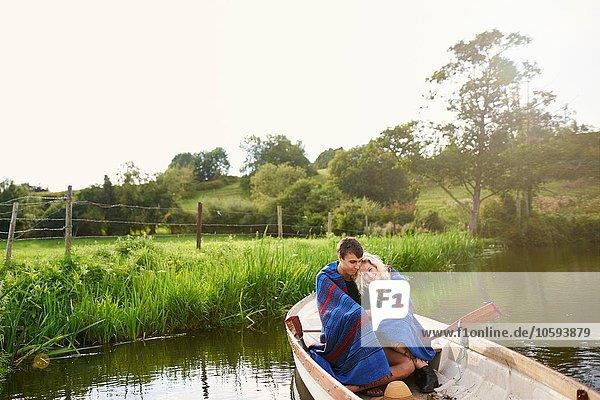 Junges Paar in Decke gewickelt und gekuschelt im Fluss-Ruderboot