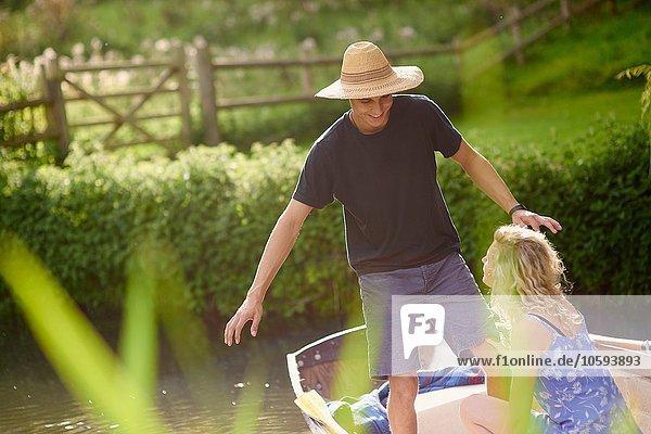 Junger Mann mit Freundin steht im Ruderboot auf dem Fluss
