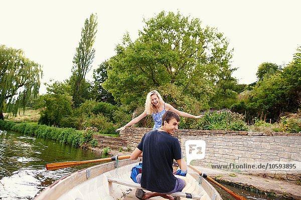 Rückansicht der jungen Frau mit ihrem Freund im Ruderboot auf dem Fluss