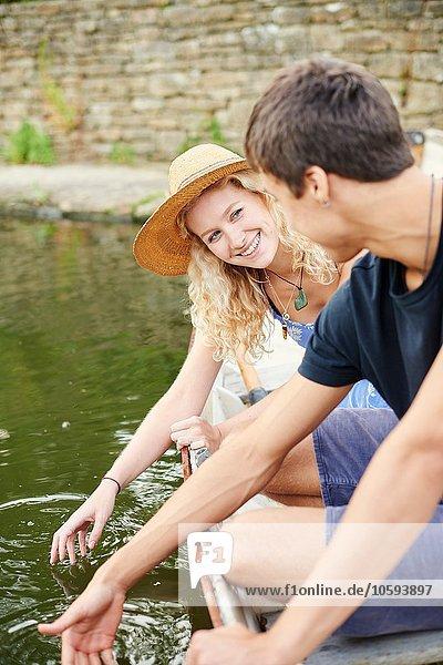 Junges Paar berührt Wasser vom Ruderboot auf dem Landfluss