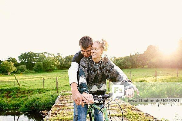Junges Paar teilt sich das Fahrrad an der Flussbrücke