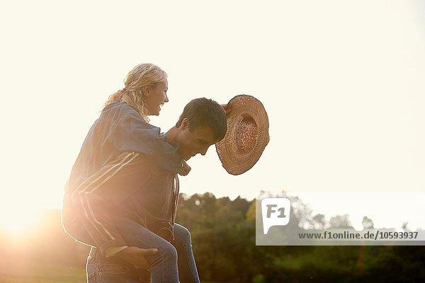 Junger Mann gibt Freundin ein Huckepack