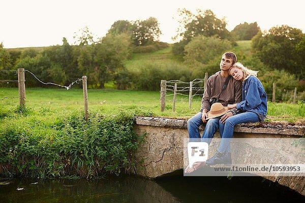 Romantisches junges Paar auf einer Flussbrücke sitzend