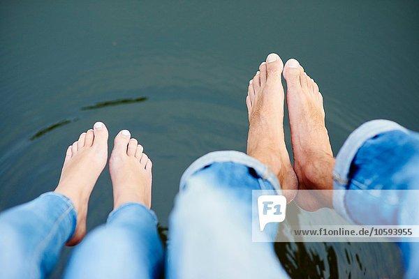 Draufsicht auf die nackten Füße und Beine des jungen Paares auf der Flussbrücke