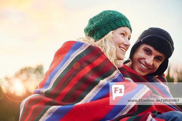 Porträt eines romantischen jungen Campingpaares in Decke gehüllt