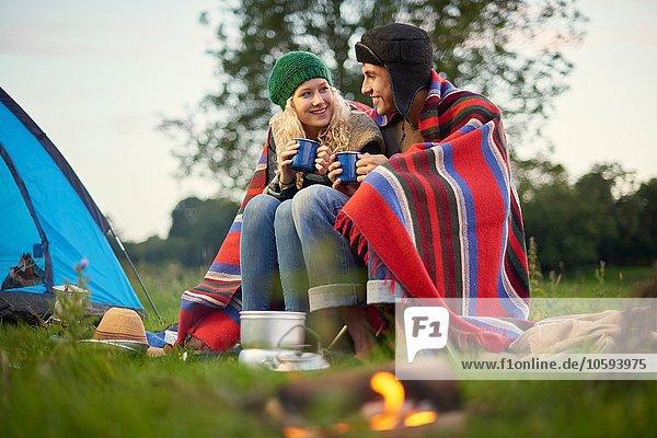 Junges Campingpaar am Lagerfeuer sitzend mit einer Tasse Tee