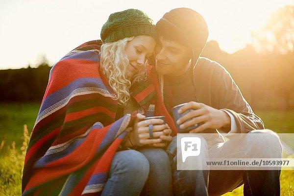 Romantisches junges Camping-Pärchen in Decke gehüllt mit Teegetränken