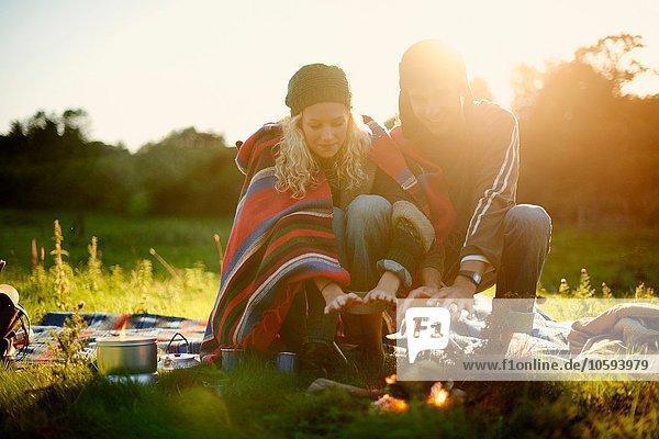 Junges Camping-Paar wärmt die Hände am Lagerfeuer in der Abenddämmerung
