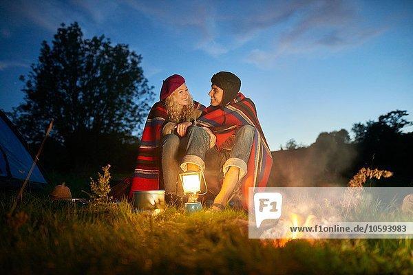 Junges Camping-Pärchen am Lagerfeuer in der Abenddämmerung