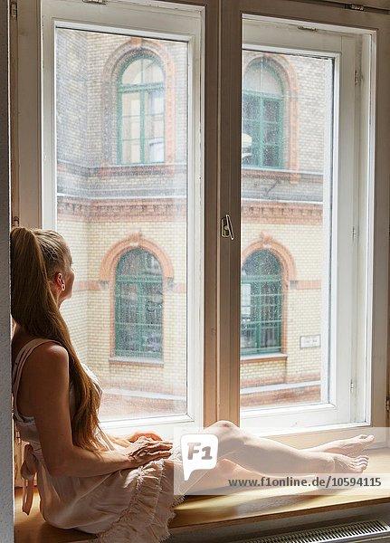 Mittlere erwachsene Frau auf dem Fensterbrett sitzend  Blick aus dem Fenster  Rückansicht
