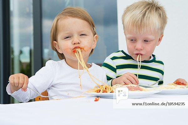 Junge und Kleinkind essen Spaghetti auf der Terrasse