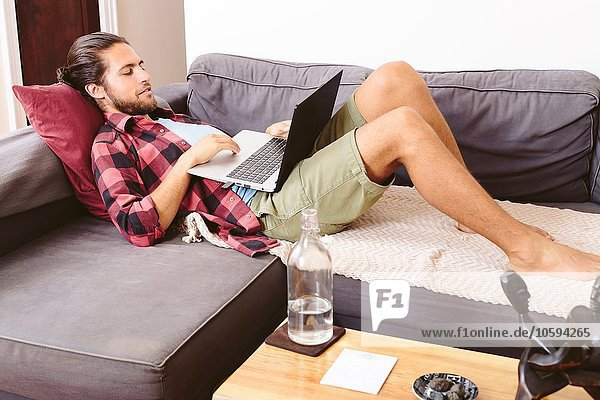 Young man relaxing on sofa  using laptop