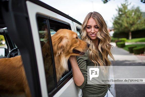 Junge Frau streichelt ihren Hund am Jeepfenster