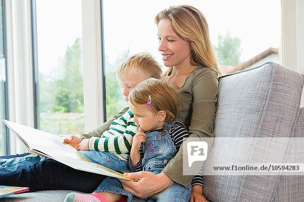 Mutter und zwei kleine Kinder sitzen auf dem Sofa und lesen ein Buch.