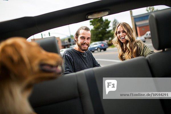 Junges Paar mit Hund bereitet sich auf Jeep-Road-Trip vor