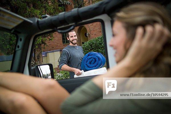 Glückliches junges Paar bereitet Jeep für die Reise vor