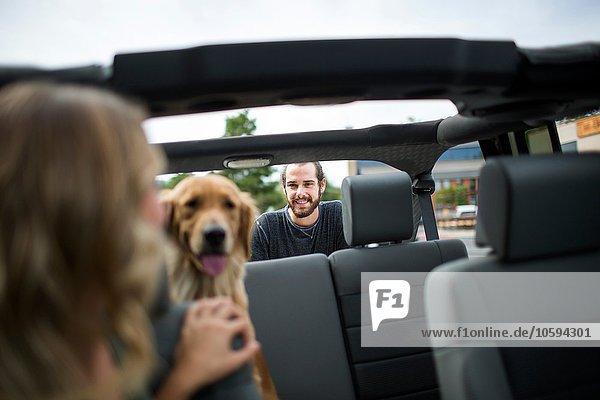 Junge Frau im Jeep mit Blick über die Schulter auf Hund und Freund
