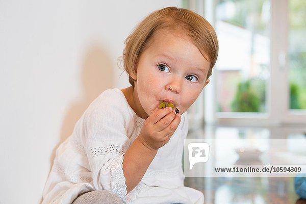Porträt des weiblichen Kleinkindes beim Pflaumenessen in der Küche