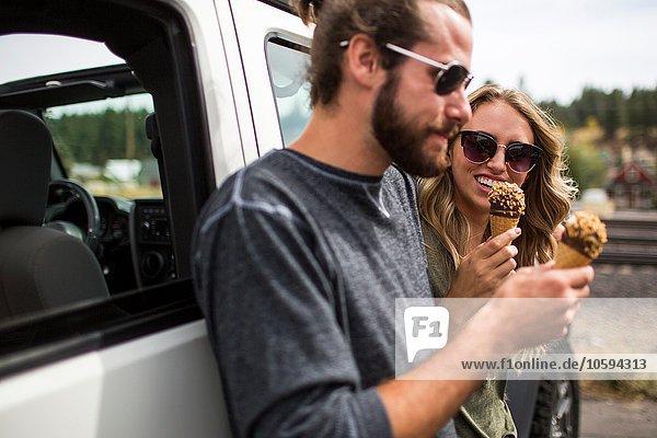 Junges Paar  das sich gegen den Jeep lehnt und Eistüten isst.