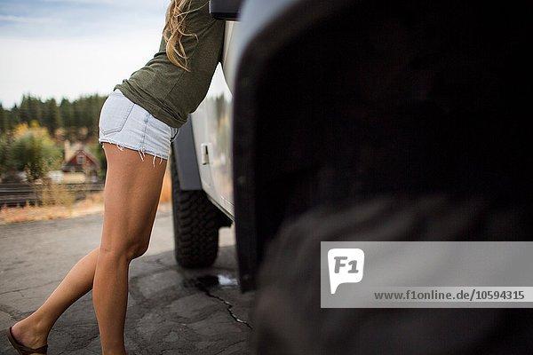 Nackenansicht einer jungen Frau in Shorts  die sich auf dem Jeep nach vorne lehnt.