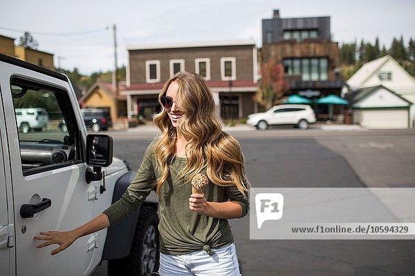 Junge Frau mit langen blonden Haaren hält Eis neben dem Jeep