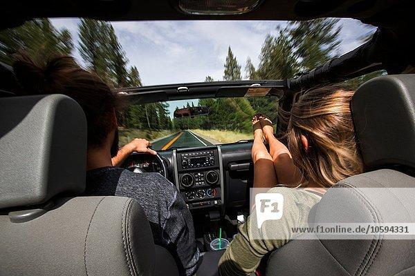Rückansicht des jungen Paares auf der Straße im Jeep