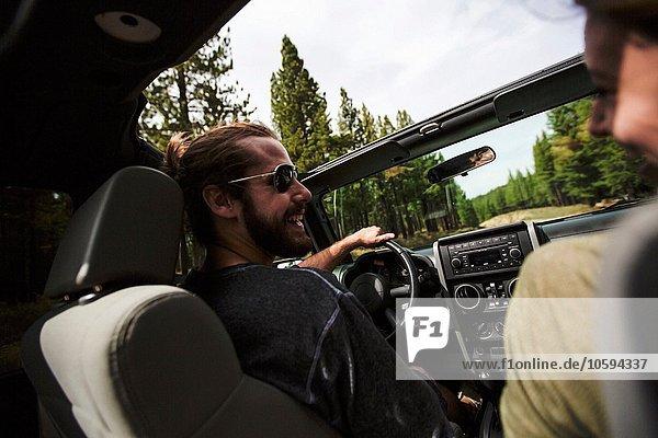 Blick über die Schulter auf das junge Paar im Jeep