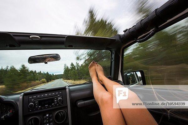 Junge Frau mit erhobenen Füßen während der Fahrt im Jeep