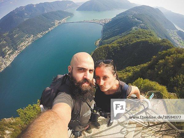 Hochwinkelaufnahme des mittleren erwachsenen Paares mit Selfie über dem Luganer See  Schweiz