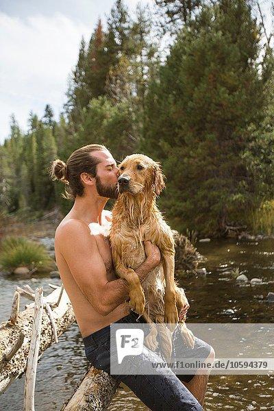 Junger Mann küsst seinen nassen Hund am Fluss  Lake Tahoe  Nevada  USA