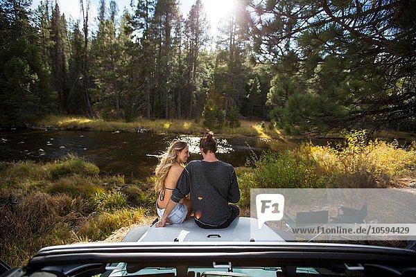 Rückansicht eines romantischen jungen Paares auf einer Jeephaube am Flussufer  Lake Tahoe  Nevada  USA